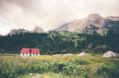 Rocky Mountains Camping Valley mit touristischen Zelten und Haus Landschaft Lizenzfreie Stockfotos