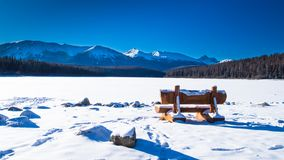 The Rocky Mountains in Canada. Bench close to the lake in Canada. Sunny day in winter royalty free stock photo