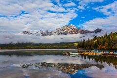 Rocky Mountains, Canada. The morning mist rises beautifully. Pyramid Mountain is reflected in the smooth cold water of Pyramid Lake. Rocky Mountains, Canada. The stock photography