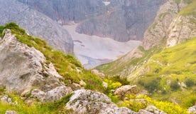 Rocky Mountains in Caucaso con la neve del ghiacciaio e la valle verde Fotografie Stock