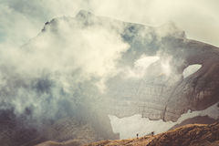 Rocky Mountains with clouds and hikers silhouette beyond Royalty Free Stock Photography