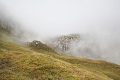 Rocky mountains in dense fog Stock Photography