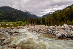 Rocky mountains. National park, river running through the meadow with sunset sky stock photos