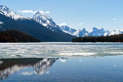 Rocky mountains reflecting in Maligne lake - Jasper national park, Canada. Snow covered Rocky mountains peaks reflected on the half frozen Maligne lake - Jasper Royalty Free Stock Images