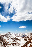 Rocky mountains. Snow caped mountains at eye level with contrasty blue sky and peaks stock photo