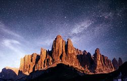 Rocky Mountains at sunset.Dolomite Alps, Italy. Rocky Mountains at sunset. Dolomite Alps, Italy. Vibrant night sky with stars and nebula and galaxy. Deep sky Royalty Free Stock Photo