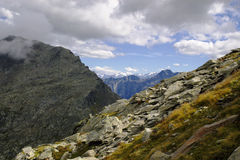 Rocky mountains under clouds. High mountain panoramic  landscape with clouds and many big rocks in front Stock Images