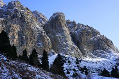 Rocky mountains of Zaili Alatau covered by snow with line 9f pine trees forest. Winter scene of peaks in Kazakhstan Stock Photography