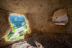 Rocky necropolis. Inside view of a rock-cut tomb in the necropolis of Pantalica in southeast Sicily Royalty Free Stock Photo