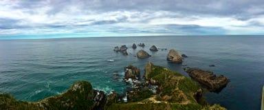 Rocky New Zealand Coastline com Rocky Islands Going Out pequeno ao mar foto de stock royalty free