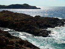 Rocky shore on the sea in great light with a lonely angler. Rocky north coast of Sardinia in low-standing sun, dark brown rocks on the blue and green sea, Sea stock images