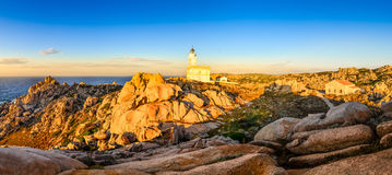Rocky ocean coastline panorama with lighthouse at sunset Royalty Free Stock Image