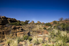 Rocky Outcrop - Landscape. Rocky terrain with small shrubs in the foreground, beautiful bright blue sunny shy in the background Royalty Free Stock Photo