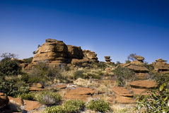 Rocky Outcrop - Landscape. Rocky terrain with small shrubs in the foreground, beautiful bright blue sunny shy in the background Stock Photos