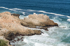 Rocky outcrop in the sea next to Clarence Drive Stock Images