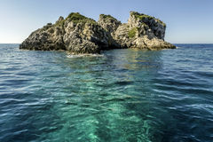 Rocky outcrop in shallow sea stock photography