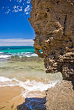 Rocky overhang on a tropical beach. Interesting rough weathered rocky overhang on a tropical beach with clear surf lapping the golden sand and an azure ocean Stock Photo