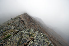 Rocky pass in haze and fog.Sayan mountains.Russia. Stock Photos