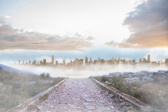 Rocky path leading to large urban sprawl. Under cloudy sky Royalty Free Stock Image