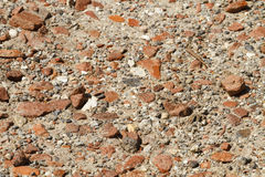 Rocky Path with Pieces of Broken Clay Bricks Close Up. Close up shot of a sandy, rocky path with numerous pieces of broken clay bricks embedded on a sunny summer Stock Photo