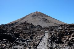 Rocky path to blurred mountain peak volcano stock photo