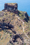 Rocky path to the cliff rock on Santorini island. Exotic rocky path to the cliff rock on Santorini island. Sea on background Stock Image