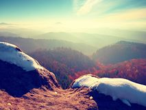 Rocky peak above inverse mist. Winter cold weather in mountains, colorful fog. Misty valley. In winter mountains. Peaks of mountains above creamy mist stock image