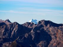 Rocky peak of Alps mountain in sunny day. Rock under fresh powder snow. Stock Images