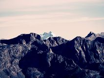 Rocky peak of Alps mountain in sunny day. Rock under fresh powder snow. Royalty Free Stock Image