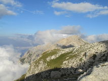 Rocky peak and green valley of Apennine Mountain Range surrounded by clouds Stock Photos