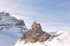 Rocky peak in snowy mountain Stock Images