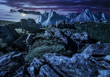 Rocky peaks and rocks on hillside in Tatras at night. Composite image of rocky peaks and rocks on hillside in High Tatra mountain ridge at night in full moon Stock Photos