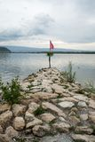 A rocky pier leading out into a calm lake with a flag pole and flag at the end and a beautiful rolling hill and lake landscape beh stock images