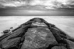 Rocky Pier sobre el agua apacible Foto de archivo