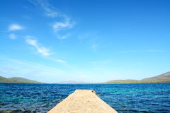 Rocky pier under soft clouds Royalty Free Stock Image