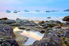 rocky plażowy słońca Piękny złocisty zmierzch przy skalistą brzegową Selekcyjną ostrością Zdjęcia Stock