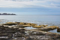 Rocky pools by the sea with two pool ladders. The photo was taken in Malta stock image