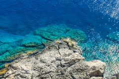 Rocky reef under Lindos acropolis on Rhodos island with blue sea. Horizontal photo with view down on rocky reef with blue sea around. Reef is under acropolis in royalty free stock photo