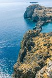 Rocky reef under Lindos acropolis on Rhodos island. Vertical photo with view down on rocky reef covered by dry grass and with blue sea around. Reef is under stock photo