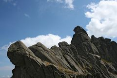 Rocky ridge and peak against blue sky with clouds Royalty Free Stock Images