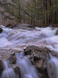 Rocky river in Franconia Notch. River carrying the melted snow from the White Mountains in early spring forming silky waterfalls along the rocky path franconia stock photos