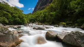 Rocky river landscape in rainforest, New Zealand. Rocky river landscape in rainforest with mountains background. Shot at Tutoko River near Milford Sound in Stock Photography