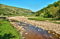 Rocky riverbed of the River Swale. Rocky riverbed and clear water of the River Swale as it flows along the valley floor between the rolling hills of the stock photo