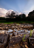 Rocky Riverbed Sunset. Sun setting behind a treeline along a rocky riverbed in Oklahoma Stock Photo