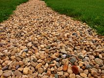 Rocky road to nowhere. Lined with grasses and stones Stock Photos