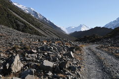 Rocky road. Towards snowing Mt. Cook in New Zealand Royalty Free Stock Images