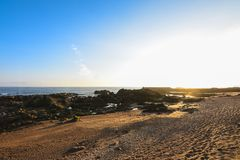 Rocky and sandy beach at sunset, with a blue sky, in Porto, Portugal royalty free stock images