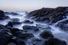 Rocky sea beach at dusk Stock Images