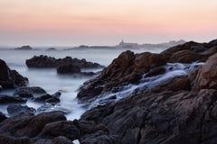Rocky sea beach at dusk Stock Photos