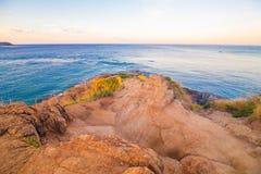Rocky sea beach sunrise blue sky with grass. Phuket Thailand Royalty Free Stock Images